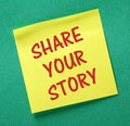 Share your story the phrase in red text on a yellow sticky note attached to a green notice board Royalty Free Stock Photo