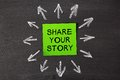 Share your story sticky note pasted on a blackboard background with a lot chalk arrows Stock Photography