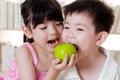 Sharing asian kids an apple Stock Photos