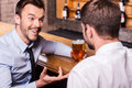 Sharing beer with good friend two cheerful young men in shirt and tie talking to each other and gesturing while drinking at the Stock Photos