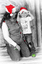 Sharing christmas joyful boy with mother in a studio wearing santa hat Royalty Free Stock Photos