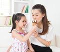 Sharing an ice cream cone eating happy asian family eating at home beautiful child feeding mother Stock Image