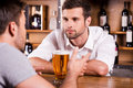 Sharing news with bartender rear view of male customer talking to while sitting at the bar counter Stock Images