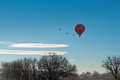 Sharing the skies a pink hot air balloon in flight with sandhill cranes Stock Image
