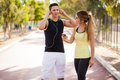 Sharing some music with my girl young couple playlists between their smartphones before working out together Stock Photos