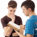 Sharing spiritual truth young men that explains god s word to his friend who thinks at Royalty Free Stock Image