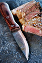 Sharp knife and juicy steak Royalty Free Stock Photo