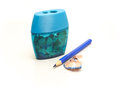 Sharpener and sharpened blue pencil with a shaving Royalty Free Stock Photo