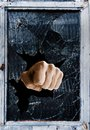 Shattered glass fist punching through a window Stock Photo