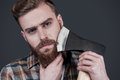 Shaving with axe confident young bearded man carrying a big on shoulder and looking at camera while standing against grey Stock Photography