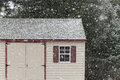 Shed in falling snow lightly on the roof of a backyard Stock Photos