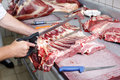 Sheep carcass a butcher cutting the ribs of using the saw Stock Photo