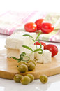 Sheep cheese in selective sharpness fotografed with olives and tomatoes Stock Photos
