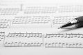 Sheet music and pen an focus on foreground Stock Photography