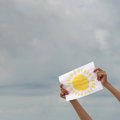 Sheet of paper with sun image against overcast sky human hands positive thinking concept Royalty Free Stock Images