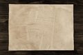 Sheet vintage paper on the aged wooden background. Parchment Royalty Free Stock Photo
