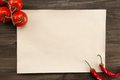 Sheet vintage paper with tomatoes and Chile peppers aged wooden background. Healthy vegetarian food. Recipe, menu, mock up, co Royalty Free Stock Photo