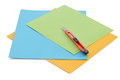 Sheets of colored paper and small stationery knife. Royalty Free Stock Photo