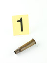 Shell casing evidence perspective aerial view of a rifle bullet and a number one tag against a white background Stock Photography