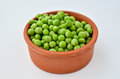 Shelled peas in a rustic clay pot over white background Royalty Free Stock Images