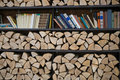 Shelves for books and firewood stacked in a pile Royalty Free Stock Photo