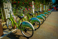 SHENZEN, CHINA - 29 JANUARY, 2017: City bike parking, row of green bikes connected to automatic machines on city street Royalty Free Stock Photo
