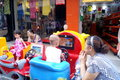Shenzhen china children playing with the toy car in july st xixiang market in front of shop their parents accompany beside Royalty Free Stock Image