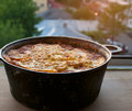 Shepherd s pie in a pot on the balcony with meat potatoes tomatoes eggs cream placed under sunset light Stock Photo