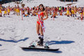 Young happy pretty women on a snowboard in colorful bikini. Royalty Free Stock Photo
