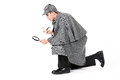 Sherlock agente investigativo using magnifying glass per esaminare qualcosa Fotografia Stock