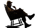 Sherlock holmes reading silhouette sitting in rocking chair in studio on white background Stock Photos