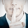 Shhhh young businessman with finger on his lips Stock Photo