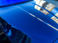 Shimmering car hood a with reflections of buildings on it Royalty Free Stock Photography