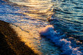 Shimmering shoreline light of the setting sun hitting to the soft waves of the sun and creates reflections on its surface Royalty Free Stock Photography