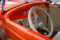 Shiny bright orange vintage sportscar side interior view of with offwhite steering wheel and upholstery Stock Images