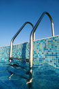 Shiny chrome ladder into pool, blue sky Stock Image