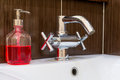 Shiny faucet and soap dispenser in the bathroom Royalty Free Stock Photo