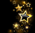 Shiny gold star with small stars on a black background Royalty Free Stock Images