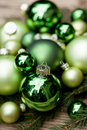 Shiny green christmas baubles closeup macro and tree on wooden background Stock Photos
