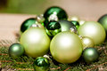 Shiny green christmas baubles closeup macro and tree on wooden background Royalty Free Stock Images