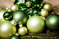 Shiny green christmas baubles closeup macro and tree on wooden background Royalty Free Stock Photos
