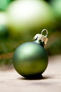 Shiny green christmas baubles closeup macro and tree on wooden background Royalty Free Stock Photography