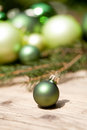 Shiny green christmas baubles closeup macro and tree on wooden background Royalty Free Stock Photo