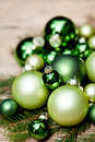 Shiny green christmas baubles closeup macro and tree on wooden background Royalty Free Stock Image
