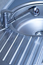 Shiny new stainless steel chrome faucet sink drain board shades blue Stock Images