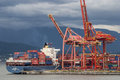 Ship docked at container loading facility cargo with containers dock in vancouver british columbia Stock Image