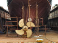 Ship in dry dock the hull and propeller of a vessel a being prepared for maintenance and repair works Royalty Free Stock Images