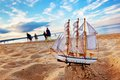 Ship model on summer beach at sunset sunny ocean in the background travel voyage vacation concepts Stock Photos