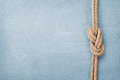 Ship rope knot on wooden texture background Royalty Free Stock Photo