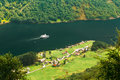Ship sailing between fjords. Village near Sognefjord fjord in No Royalty Free Stock Photo